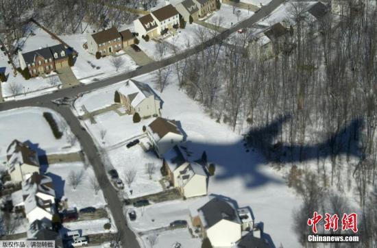 """资料图:""""空军一号""""在马里兰州被白雪覆盖的华尔道夫酒店上空。"""