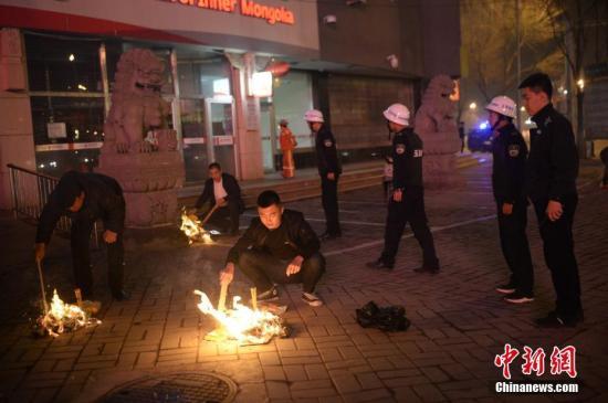 资料图:城管执法人员劝阻民众停止在街边焚烧纸钱。中新社记者 刘文华 摄