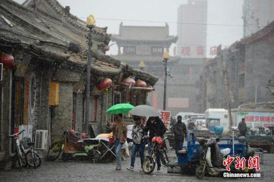 4月3日,雪中的明清古街,民众撑伞步行。当日,呼和浩特迎来降雪,气温骤然下降,不少民众纷纷加衣保暖。中新社记者 刘文华 摄