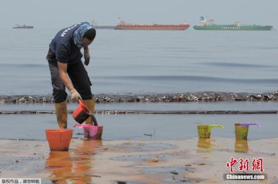 警察在Banua Patra海滩清理浮油。