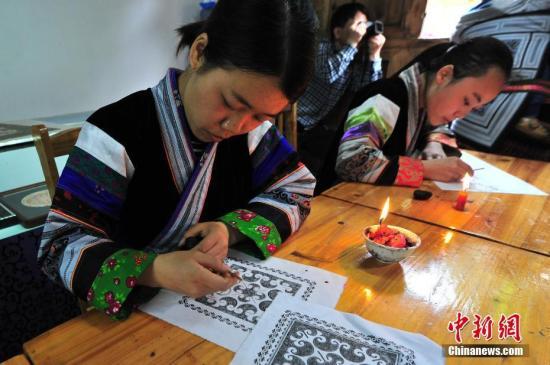 """贵州织金:""""指尖经济""""绘制幸福新生活。图为4月11日手工艺人在绘制蜡画。陈威 摄"""