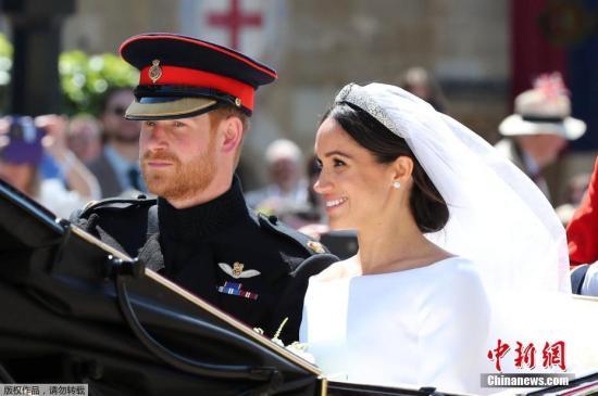 资料图:当地时间5月19日,英国哈里王子与美国女星梅根·马克尔在英国温莎城堡举办婚礼。新人乘坐马车亮相。