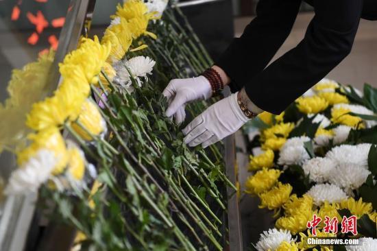 资料图:用鲜花送别死者最后一程。 武俊杰 摄