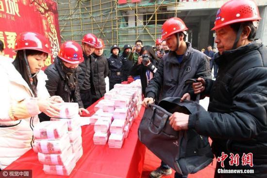 2017年1月,西安一工地发放1200万工资奖金,工人用旅行包装。马昭 摄 图片来源:视觉中国