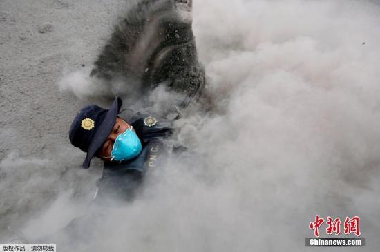 """当地时间6月4日,一名危地马拉警察在逃离新一轮火山灰碎屑时蹒跚而行,继而被火山灰冲倒。当地时间3日,危地马拉的""""火峰""""火山爆发,该国灾难机构称,附近社区约3100人被疏散。火山喷发影响地区的人口约为170万人。"""