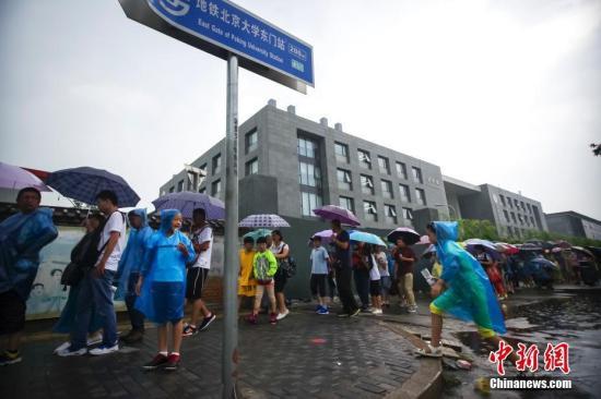 8月12日,游客冒雨在清华大学校门外排队等候入校参观。暑假以来,不少游客带着子女蜂拥至北京大学、清华大学等高校,一睹中国最高学府的风采。 中新社记者 贾天勇 摄