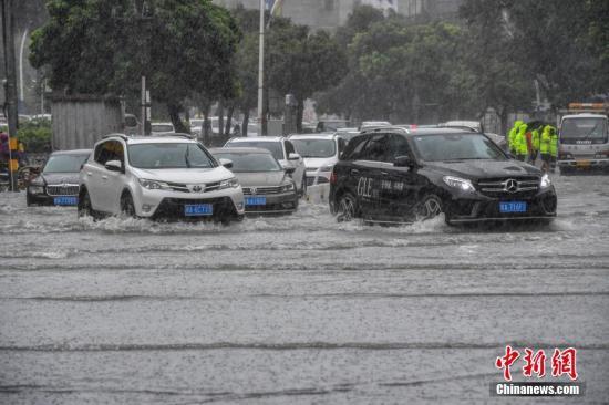 车辆涉险通过海口市龙华路积水路段。骆云飞 摄