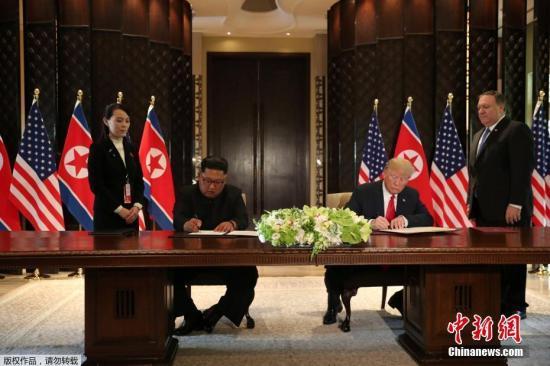 """美国总统特朗普与朝鲜最高领导人签署文件。金正恩在签字前称,""""世界将见证巨大的改变""""。"""