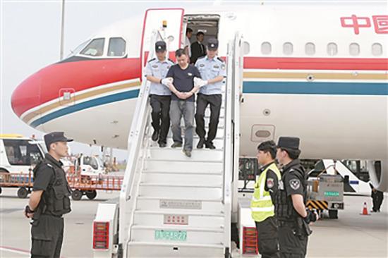 图为6月18日,在南京禄口机场,两名公安人员押解王颀走下飞机舷梯。徐锦华 摄