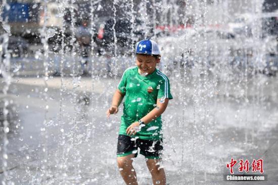 资料图片:市民玩水,以躲避高温。