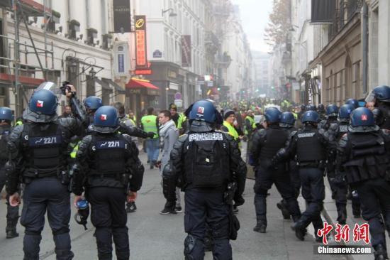 原料图:当地时间11月24日,巴黎香榭丽弃大街遭遇大周围示威运动。图为法国警方当天在香榭丽弃大街附近与大批示威者对峙。中新社记者 李洋 摄