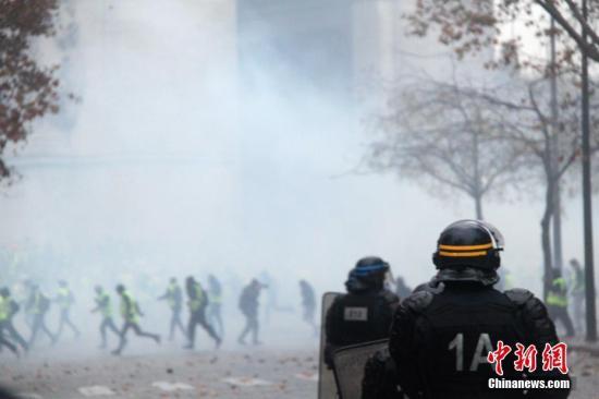 示威者荟萃在凯旋门。巴黎警倾向示威者施放催泪瓦斯,试图将示威者驱散。 中新社记者 李洋 摄