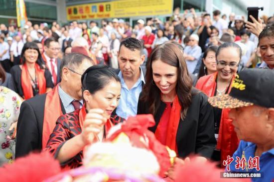 """2月2日,作爲新西蘭奧克蘭市一年一度最具人氣的中國新年慶祝活動——2019""""歡樂春節""""新春花市同樂日活動在奧克蘭ASB會展中心開幕,新西蘭總理傑辛達·阿德恩爲花市舞獅團雄獅掛上節日繡球。中新社發 張健勇 攝"""
