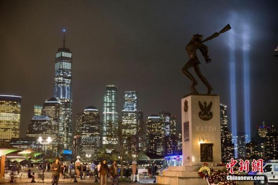 """资料图:当地时间2018年9月11日,美国""""911事件""""17周年,纽约世贸中心附近两根象征着世贸中心双子塔的蓝色光柱直冲云霄,一直持续到黎明。图为从泽西市透过城市雕塑遥望灯柱。中新社记者 廖攀 摄"""