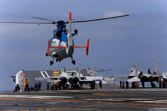 4月26日,辽宁舰航母编队圆满完成远海实兵对抗训练,返回青岛航母军港。在连续10多天高强度和高难度的实兵对抗演练中,航母编队体系作战能力得到进一步强化、提升和检验。图为4月21日,舰载直升机飞行归来。视觉中国供图