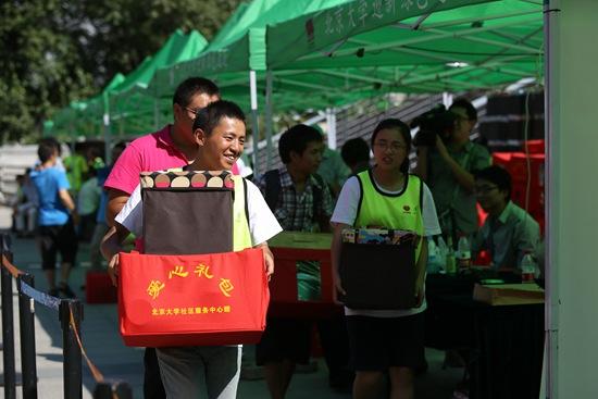 """2018-09-26,北京大学,一名大一新生在北大迎新""""绿色通道""""内领到了爱心礼包。视觉中国供图"""