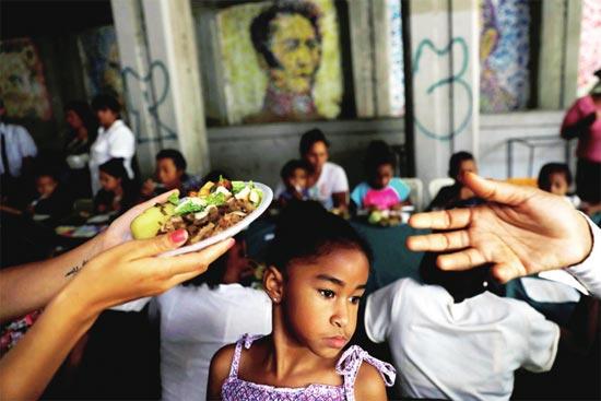 2018年5月13日,在委内瑞拉加拉加斯,代表总统候选人哈维尔·贝尔图奇的志愿者向妇女儿童分发食物。图片来源视觉中国