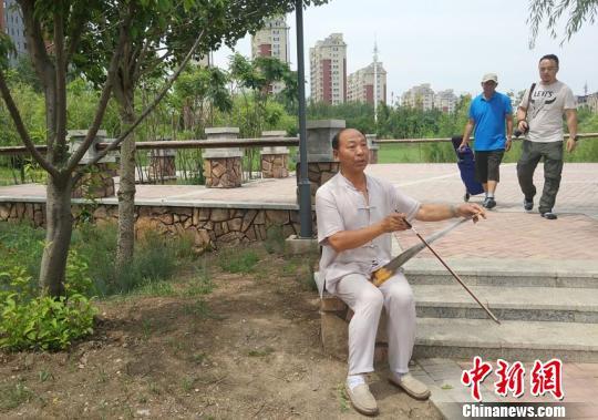 梁林生在长春的一处公园内练习锯琴。 李明姝 摄