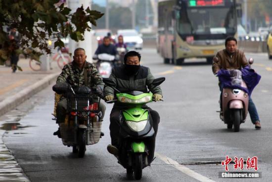 11月6日,河南多地遭遇阴雨天气,气温骤降。郑州的市民纷纷穿上厚衣服抵御寒冷。中新社记者 王中举 摄