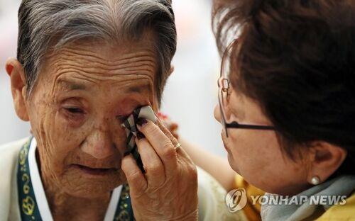 (8月25日,朝韩离散家属在朝鲜金刚山离散家属会面所举行集体会面,77岁的韩国老人朴某为85岁的朝鲜姐姐拭泪图片来源:韩联社)