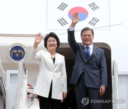 资料图片:2017年6月28日,在首尔机场,韩国总统文在寅(右)和第一夫人金正淑登机之前向欢送人群挥手致意。当天文在寅启程前往美国,开启为期五天的访美之行。(图片来源:韩联社)