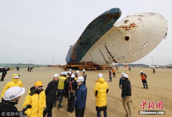 """资料图:当地时间2018年2月21日,作业人员在韩国全罗南道木浦新港准备将""""世越""""号移动至模件运输车(MT)上。当天将""""世越""""号打横移动后,工作人员准备于5月31日扶正船体。 图片来源:视觉中国"""