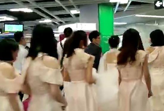 新郎新娘被伴郎伴娘簇拥着进入地铁。视频截图