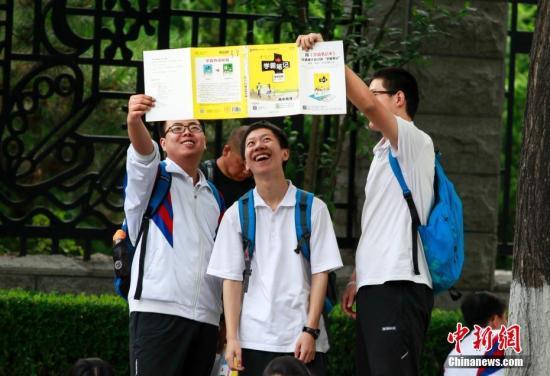 6月8日,全国高考迎来第二天考试日程,北京一考点外考生入场前正在进行最后的复习。 中新社记者 贾天勇 摄