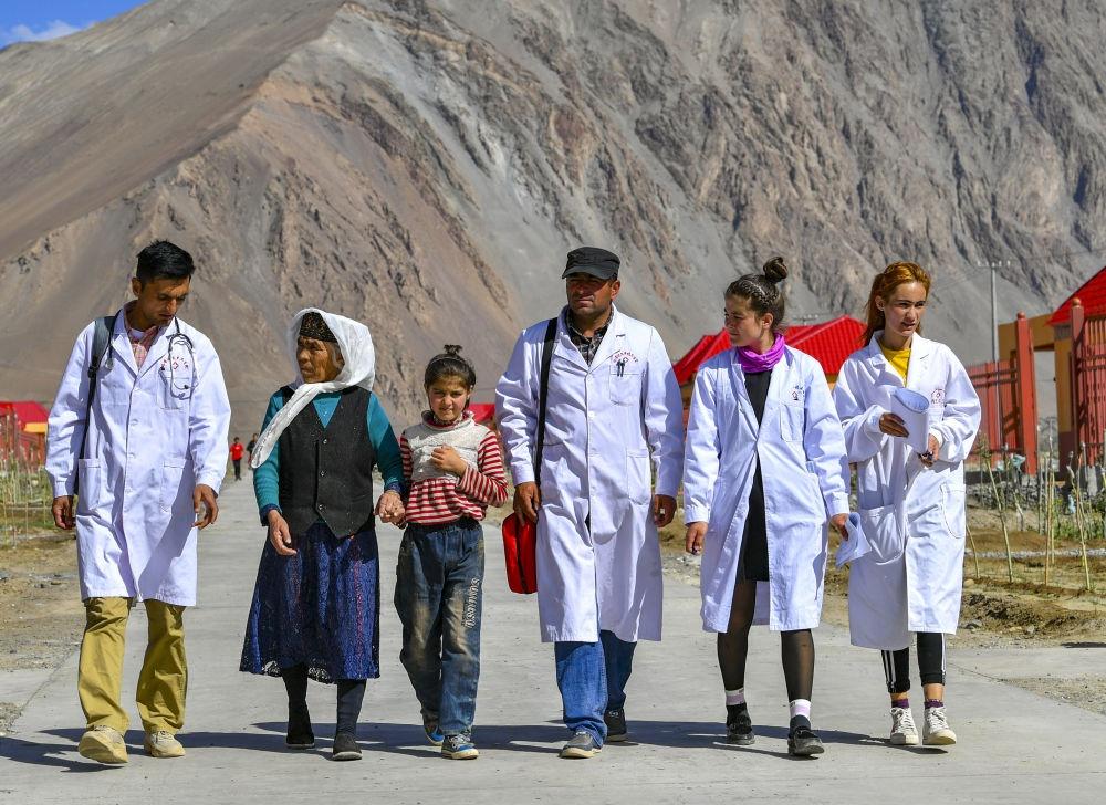 新疆塔什库尔干塔吉克自治县达布达尔乡热斯喀木村村医发尔亚特·塔西白克(右三)与医务职员来到本地易地扶贫搬家安顿点出诊(2019年7月7日摄)。新华社记者 胡虎虎 摄