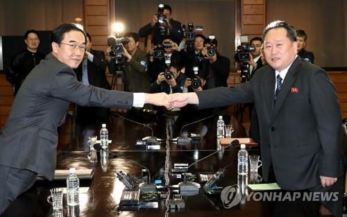 今年3月29日,韩国统一部长官赵明均(左)与朝鲜祖国和平统一委员会委员长李善权(右)在板门店举行的朝韩高级别会谈上握手致意。(图片来源:韩联社)