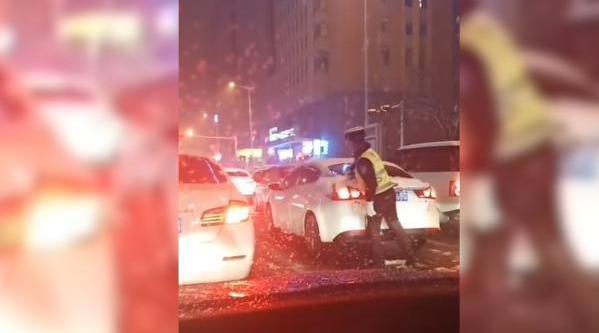 大雪天,辅警为过往车辆除积雪1小时
