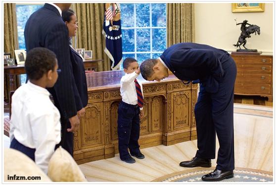 奥巴马弯腰让一名白宫职员的孩子摸头。