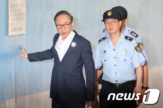 20日,李明博用手扶墙走进法院