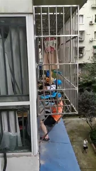 两岁半幼童翻护栏吊四楼 大爷爬空调外机托举相救