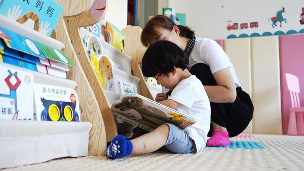 宁陕县城南养育中心,一位年轻的母亲正在陪孩子读绘本