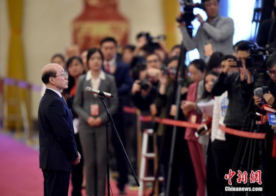 """3月5日,十三届全国人大二次会议在北京人民大会堂开幕。图为国务院台湾事务办公室主任刘结一在""""部长通道""""接受采访。 中新社记者 侯宇 摄"""