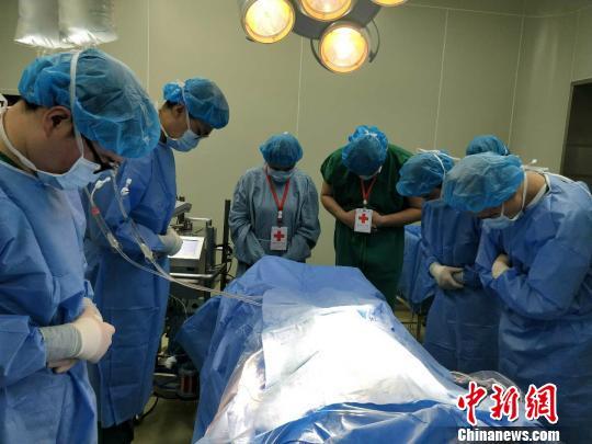 图为李永波捐献器官,工作人员默哀致敬。 巴南区委宣传部供图 摄