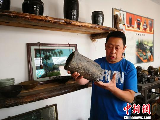图为彭维国展示他从村里废墟上淘来的冶铁工具。 魏建军 摄