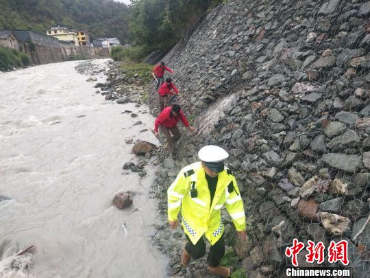 图为救援人员沿河道搜救。
