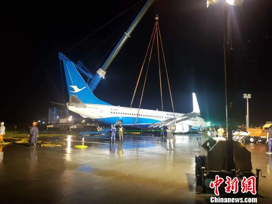 18日凌晨6时13分,马尼拉国际机场(NAIA)使用起重机及平台车将厦航降落后冲入6/24号跑道外草地的飞机,搬移至指定停放位置。 NAIA媒体中心供图 摄