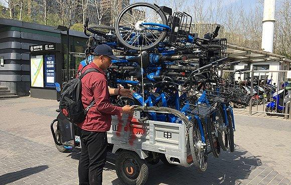 北京地铁望京南站,不时有三轮车及卡车运来小蓝车。摄/唐俊