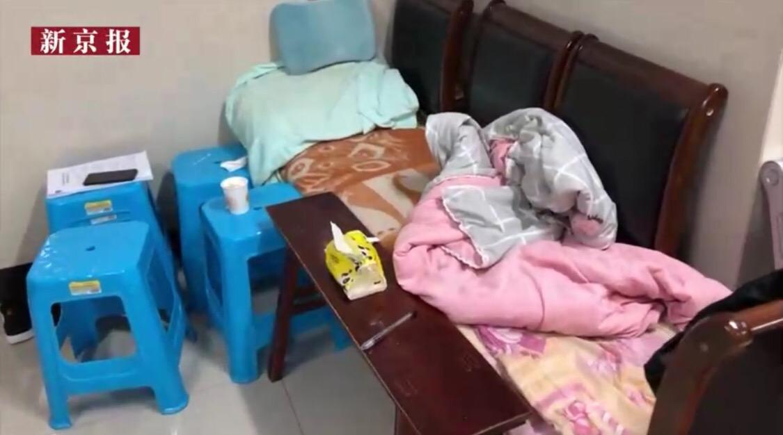 """叶万焕用四张凳子拼成一个浅易床,正在殡仪馆住了半年。 新京报""""我们视频""""截图"""