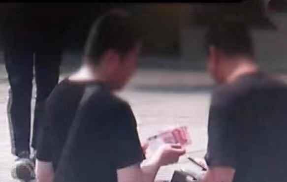 游客把钱交给乌衣须眉。视频截图