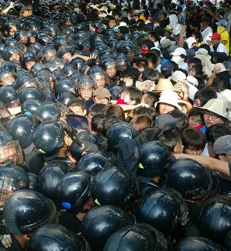 2006年8月14日,在韩国首都首尔,反美游行队伍与防暴警察发生冲突。当日,韩国民众举行了要求驻韩美军撤兵、呼吁和平的抗议示威活动。 新华社记者李拯宇摄