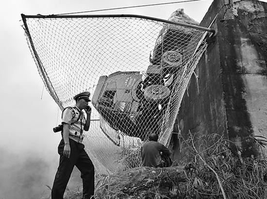 大货车失控冲出自救匝道挂在百米悬崖,墙外网兜兜住车上两人