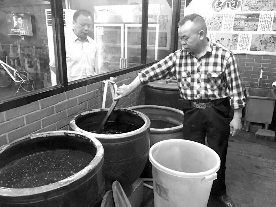 5月11日,火宫殿臭豆腐传承人何谷良正在搅拌卤水。