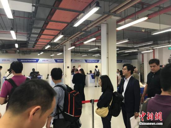 """6月10日,新加坡为""""特金会""""而设在F1维修大楼的国际媒体中心正式开放,多国媒体记者陆续抵达媒体中心等待注册,领取记者证。 中新网记者 孟湘君 摄"""