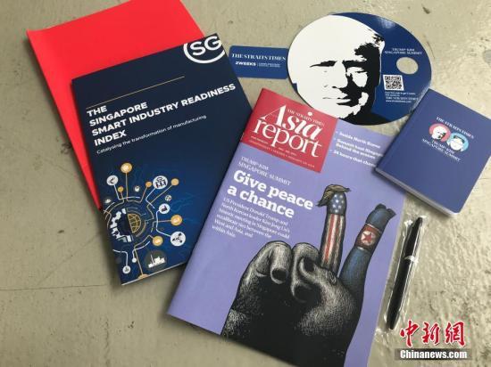 """6月10日,新加坡为""""特金会""""而设在F1维修大楼的国际媒体中心正式开放。记者从新加坡政府发放给媒体的会议礼包中看到,材料丰富,包括会议指南,印有特朗普和金正恩两位领导人头像的小笔记本,以及一把有趣的扇子,扇子的两面,分别印有特朗普和金正恩的肖像,并标注有""""特金新加坡峰会""""字样。 中新网记者 孟湘君 摄"""