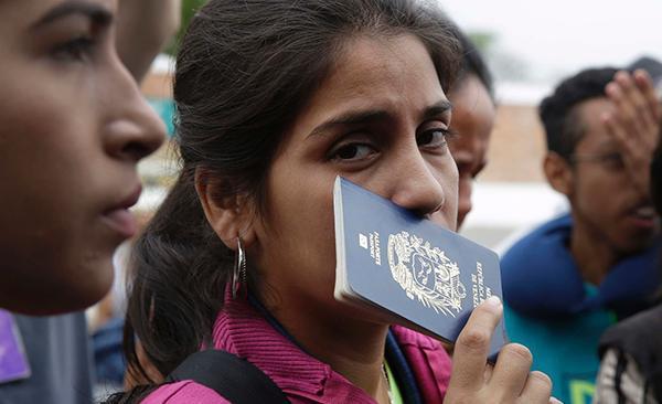 当地时间2018年8月25日,秘鲁通贝斯,一名委内瑞拉移民手持护照,排队等公共汽车。在秘鲁当局开始执行更严格的入境规定前,数千名委内瑞拉人争分夺秒地进入秘鲁。东方IC 资料图