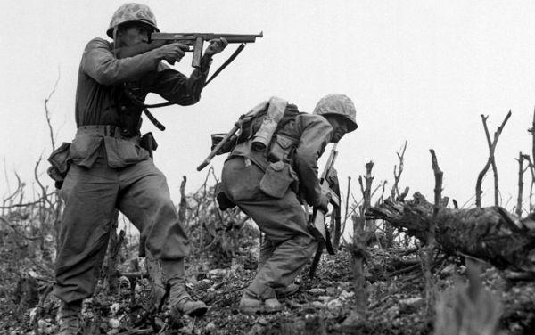 资料图片:1945年冲绳战役期间,美海军陆战队员手持汤普森冲锋枪警戒。(图片来源于网络)